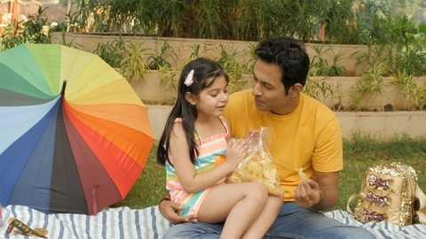 Modern Indian father offering wafers / chips to his little girl - togetherness and bonding