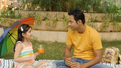 Lovely father-daughter pair drinking sweet fruit juice in a park - family moments
