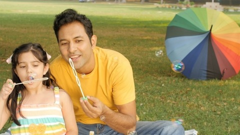 Cute little girl blowing soap bubbles with her cheerful daddy in a green area
