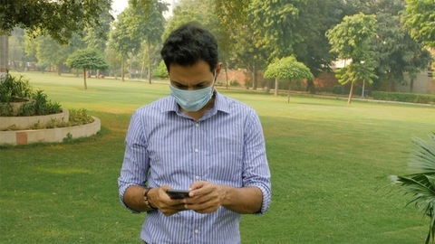 Modern Indian male wearing surgical face mask using a smartphone in COVID-19