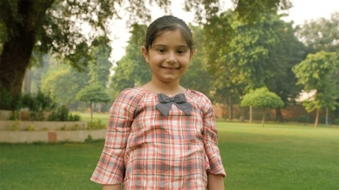 Portrait of a little girl child smiling while looking at the camera - happy mood