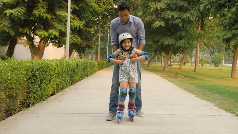 Urban Indian dad teaching his small girl to slide on roller skates - fun moments