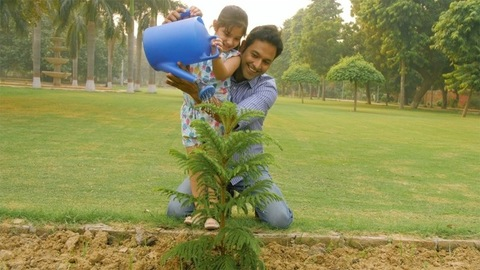 An attractive man holding his child while she is watering the plants with a can