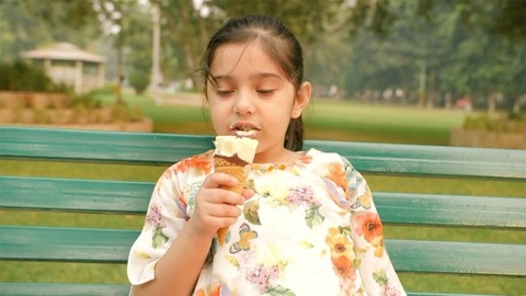 Portrait of a small girl enjoying yummy ice cream sitting on a bench in the garden