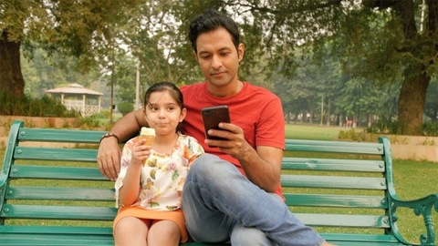 A cute little girl eating an ice-cream with her father sitting by her side