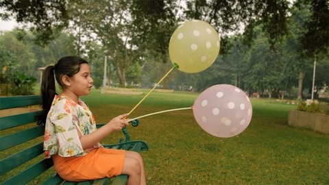 Portrait of a cute little girl holding colorful balloons while sitting in the park
