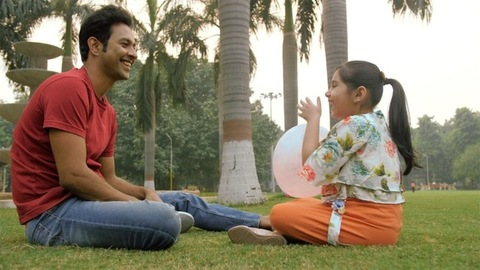 Sideview of a father-daughter playing with a balloon sitting on the grass
