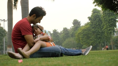 Loving father cuddling his tired and sleepy child sitting outdoors in the park