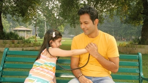 A cute small child holding a stethoscope checking her father's heartbeat