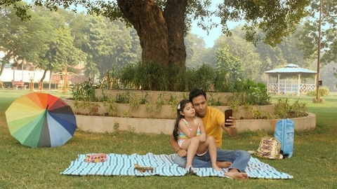Indian male in casual wear enjoying during a picnic with his little girl in a park