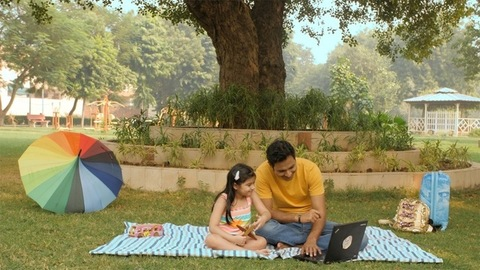 Handsome male showing things to his little daughter on a laptop sitting outdoors