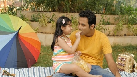 Father-daughter eating potato wafers during a picnic in a garden - family lifestyle
