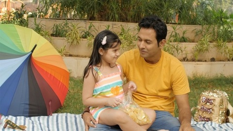 Father and daughter eat chips / wafers sitting in a garden - happy family kid