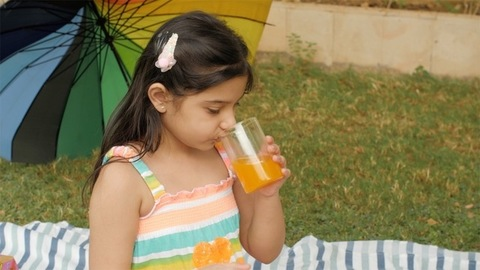 A sweet little girl drinking a glass of fruit juice and having chips in the park