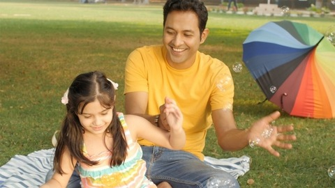 Father and daughter trying to catch bubbles flying in the air - fun moments
