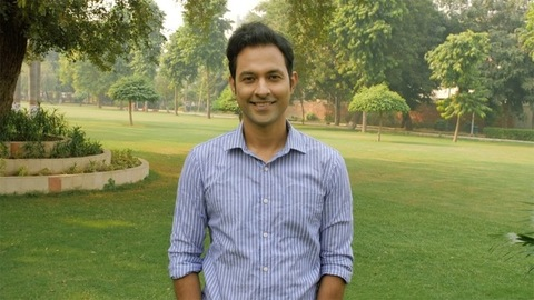 Portrait of a happy Indian male in a formal shirt posing for the camera outdoors