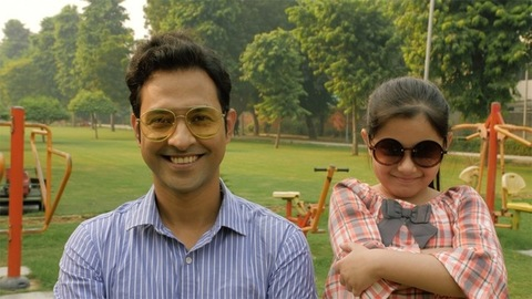 Smart urban father-daughter putting on their stylish sunglasses in a park