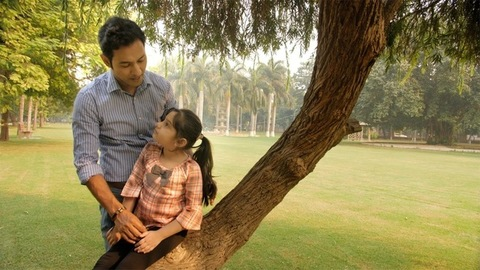 City child with a ponytail talking to her father standing near a big tree in a park