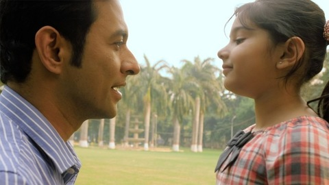 Young dad talking to his girl child sitting in a park - parenting and childhood