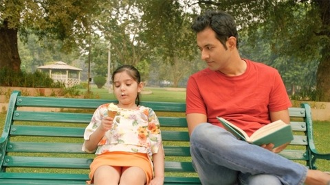 A cute little girl eating an ice-cream while her father is reading a book