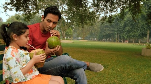 Father and daughter having natural coconut water with a straw - healthy drink