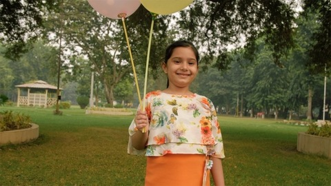 Portrait of a happy little girl standing in the park with two colorful balloons