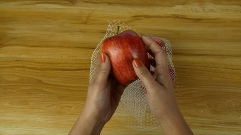 Woman hands taking out a juicy apple from a mesh bag - healthy fruits concept