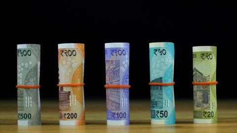 Tilt shot of various bundles of colorful Indian paper currency - finance concept