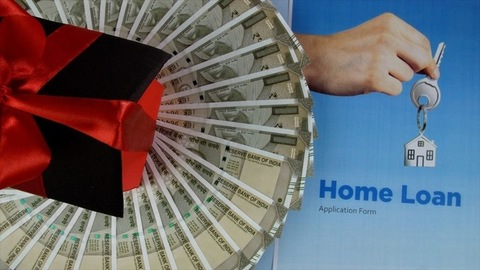 Closeup shot of a home loan application form with banknotes and a house model