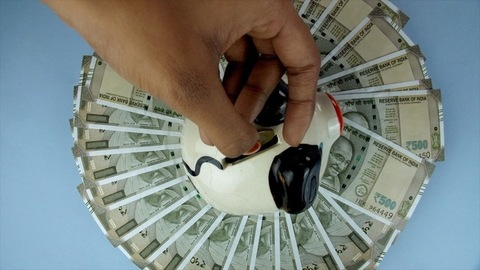 Closeup of woman hands putting 10 rupees coin in a piggy bank - saving wealth concept