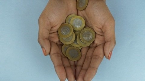 Closeup shot of Indian 10 rupee coins falling in the hands of a young woman