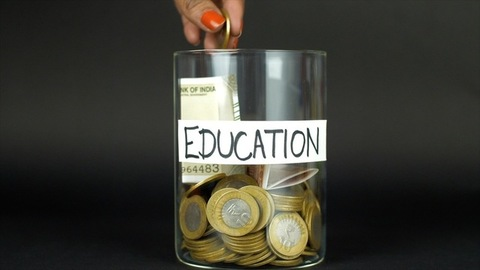 Woman hands dropping 10 rupee coins in a container with education label - grey background