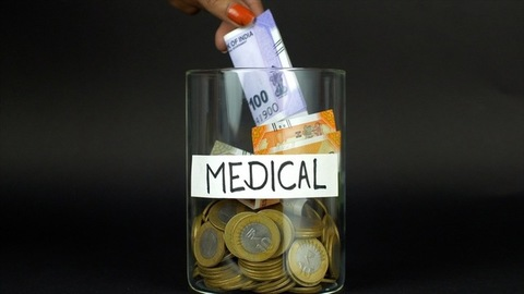 Closeup of a hand dropping banknotes and coins in a container with a medical label