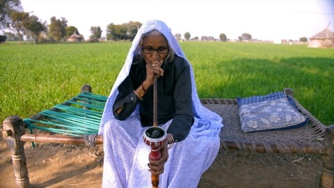 Aged Indian grandmother smoking hookah while sitting on chaarpai in a rural background
