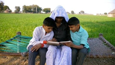 Young grandsons happily reading a book with their grandmother during daytime