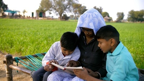Aged Indian granny happily reading a book with her grandsons - village scene