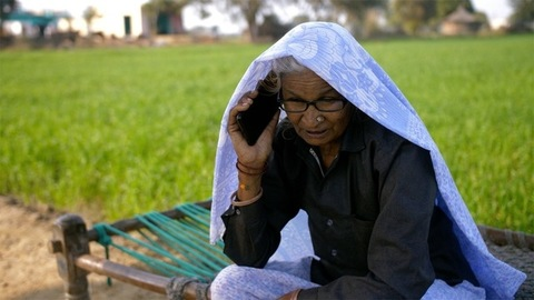 Old Indian grandmother happily talking to her relatives using her smartphone