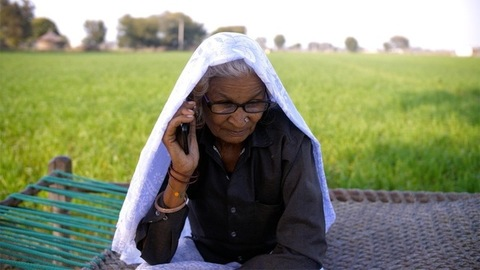 Elderly grandma busy talking on a mobile phone against a rural background