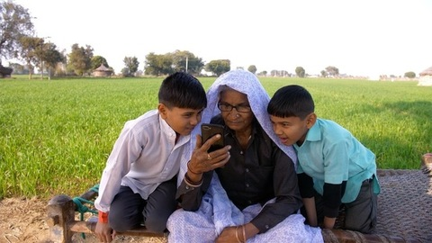 Two little grandsons with their granny waving during a video chat in a village