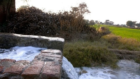 Pan shot of water coming out of a tube well and flowing in the agricultural fields