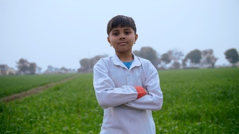 Cute Indian kid stood next to a grassy wheat field smiling in a Kurta Pajama