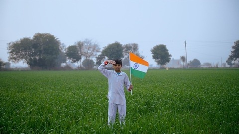 Young village boy salutes with Indian National flag - Republic / Independence day