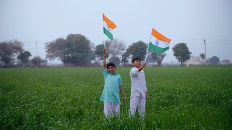 Two Indian boys proudly waving the tricolor flag on Independence/Republic day