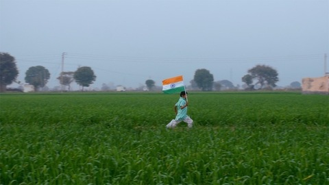 Young farm boy running with the tricolor flag of India - Independence / Republic day