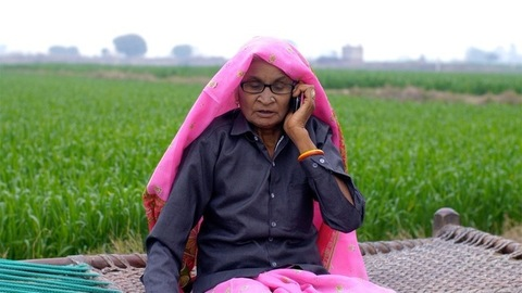 An old village woman using mobile to talk - Use of technology in the village life