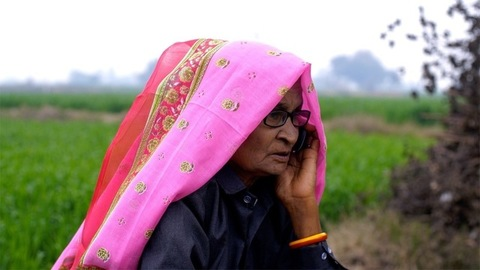 A medium shot of an old lady talking on a mobile amidst green farmlands