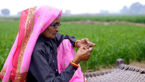 An aged woman praying in an open field sitting on a woven cot in a village