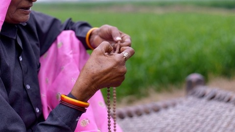 Close up shot of an aged woman, praying while using beads - Religious practice in Hindu culture