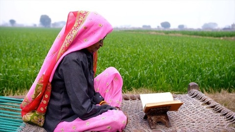 An old Indian woman sitting on a woven cot reading a religious book near a farmland