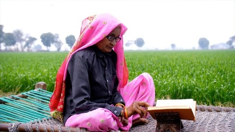An aged woman of a village reading a religious text while sitting near a farmland